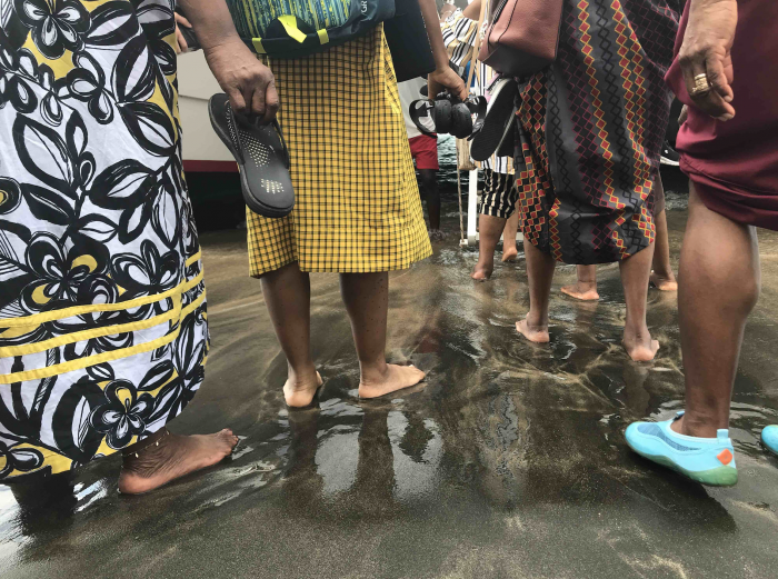 """""""Garifuna Women traveling from New York City and Los Angeles walk in  shallow water to board a boat to Baliceaux as part of pilgrimage to their ancestral home of Yurumein, known as St. Vincent and the Grenadines."""" Photograph taken by NYAS Anthropology Board Member Kristina Baines"""
